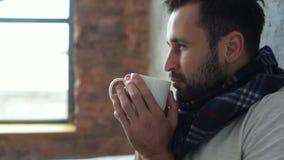 Riportato in scala su del tipo millenario rilassato nel tè bevente della sciarpa archivi video