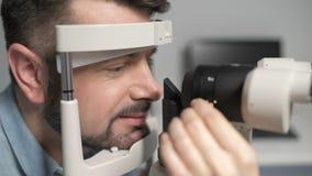 Riportato in scala su dell'uomo barbuto che subisce esame degli occhi stock footage