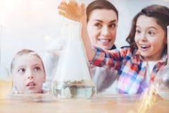 Riportato in scala sul colpo dei bambini divertendosi nel laboratorio di chimica Fotografia Stock