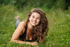 Riposarsi femminile giovane sull'erba fotografie stock