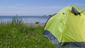 Riposi sul fiume, nella priorità alta è una tenda, nei precedenti, la barca lanciata Immagini Stock