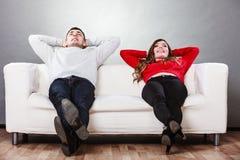 Riposo di rilassamento delle coppie felici sullo strato a casa Fotografie Stock Libere da Diritti