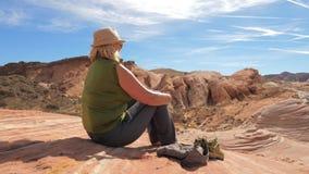Riposo di seduta del turista attivo della donna sulla roccia rossa e sulle viste piene d'ammirazione del canyon Immagine Stock Libera da Diritti