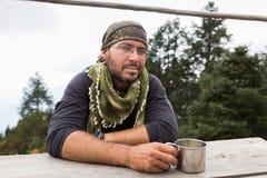 Riposo di seduta dell'alpinista di viaggiatore con zaino e sacco a pelo del ritratto turistico dell'uomo Fotografia Stock