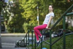 Riposo di seduta della ragazza sull'inferriata nel parco Immagine Stock Libera da Diritti