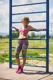 Riposo femminile sorridente dei giovani dopo un addestramento attivo di forma fisica mentre stando, donna adatta soddisfatta che  Fotografie Stock
