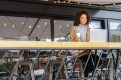 Riposo femminile su un terrazzo con il computer Fotografia Stock