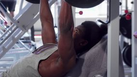 Ripped African male bodybuilder smiling to the camera after lifting barbell. Handsome muscular athletic man working out at the gym, doing bench press with stock video