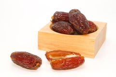 Ripped dates in the wooden plate Royalty Free Stock Photography