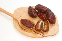 Ripped dates in the wooden plate Royalty Free Stock Image