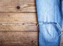 Ripped denim jeans on wooden background. Fashion, clothing, style, lifestyle Stock Photos