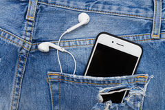 Ripped denim shorts with telephone and headphones in the pocket, Stock Image