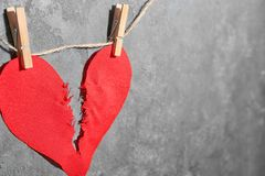 Ripped fabric heart hanging on rope. Against grey background. Relationship problems Royalty Free Stock Photos
