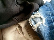 Ripped faded old clothing. Vintage old clothes with various rips, wear and tears. Jeans,khakis, fleece sweatpants ready to donate to the thrift store, to support Royalty Free Stock Photography