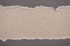 ripped gray paper on brown background Stock Image