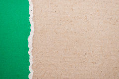 ripped green paper on brown background Royalty Free Stock Photos