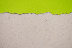 ripped green paper on brown background Royalty Free Stock Photo