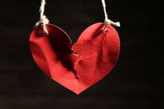 Ripped heart hanging on ropes dark background. Ripped heart hanging on ropes against dark background. Relationship problems Royalty Free Stock Images