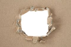 Ripped hole in brown cardboard royalty free stock image