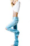 Ripped jeans. A blond young woman posing in a pair of ripped jeans, wearing a white top Royalty Free Stock Photos