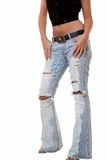 Ripped jeans. Legs of a woman wearing ripped faded jeans standing over white Royalty Free Stock Images