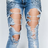 Ripped jeans. Ripped blue jeans female feet Stock Images