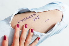 Ripped jeans. Girl wearing ripped blue jeans, red polished nails Stock Photos