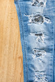Ripped jeans on wooden background. Stock Photography
