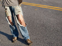 Ripped Jeans. A young man, from the waist down,  in a causal t-shirt and ripped jeans with hair legs exposed stands in the road Stock Images