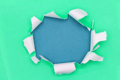 Ripped open paper. Green ripped open paper on blue paper royalty free stock image