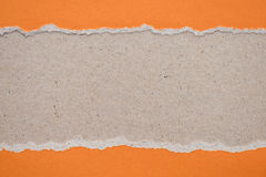 ripped orange paper on brown background Royalty Free Stock Images