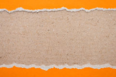 ripped orange paper on brown background Stock Photography