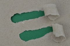 Ripped paper revealing green blank spaces for text. Ripped packing paper revealing two spots of dark green blank sheet with copy space for a message or a text Royalty Free Stock Photography