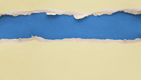 Ripped paper. Ripped yellow paper on blue background Stock Photo