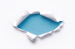 Ripped paper. Ripped white paper against a blue backgrounds royalty free stock photography