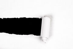 Ripped paper. Ripped white piece of paper on a black background with rough edges Stock Images