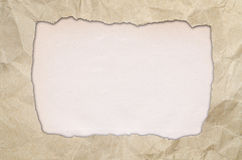 Ripped paper on brown background Royalty Free Stock Images