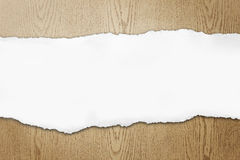 Ripped paper on wood background royalty free stock photography