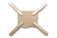 Ripped piece of card board with four clothespins Royalty Free Stock Photos