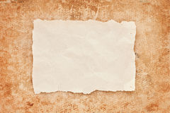 Ripped piece of old paper on grunge background. Ripped piece of old paper on grunge paper background. vintage retro card Stock Photos