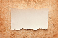 Ripped piece of paper on grunge paper background. Vintage retro card Stock Images