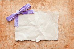 Ripped piece of paper with purple bow. On grunge paper background. vintage retro card Royalty Free Stock Photo
