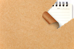Ripped Recycle Paper against a Notepad Royalty Free Stock Photo
