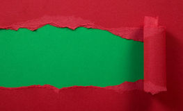 Ripped red paper with green background Stock Photo