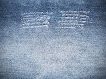 Ripped torn pattern of blue denim jeans texture and background. Close up ripped torn pattern of blue denim jeans texture and background royalty free stock photos