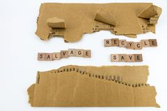 Torn cardboard salvage recycle save. Ripped weathered torn cardboard edges white copy space background wood block scrabble wooden letters salvage recycle save Stock Photos