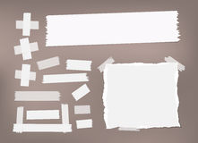Ripped white notebook, copybook, note paper, sticky, adhesive masking tape stuck on brown background Stock Photos