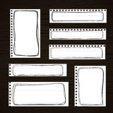 Ripped white notebook, note, copybook paper sheets with black doodle frames, stuck on dark wooden board Royalty Free Stock Photo