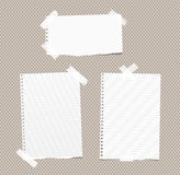 Ripped white ruled, blank note, notebook, copybook paper sheets stuck with white sticky tape on brown squared pattern Stock Photo