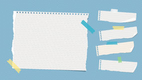 Ripped white ruled note, notebook, copybook paper sheets stuck with colorful sticky tape on blue squared pattern.  Royalty Free Stock Photography